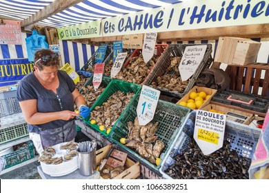 CANCALE, FRANCE - AUGUST 1, 2014: A local woman sells fresh oysters out of crates at the french coast of Brittany (Bretagne) in Cancale, France, on August 1, 2014