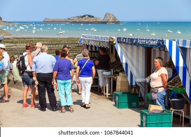 CANCALE, FRANCE - AUGUST 1, 2014: Tourists visit a farm for harvesting oysters along with a small market for selling them for consumption in Cancale, France, on August 1, 2014