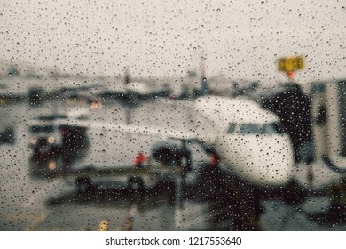 Canceled flight during weather conditions concept. Aircraft on gate under massive rain. Delay flight.