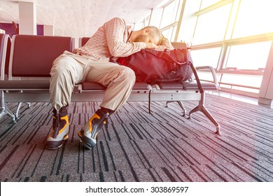 Canceled flight.  Man sleeping on his travel luggage inside airport terminal with back light bright sun coming throw window