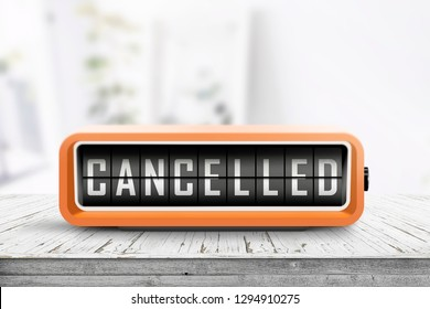 Cancelled message on a retro alarm clock in a bright room with a weathered wooden table