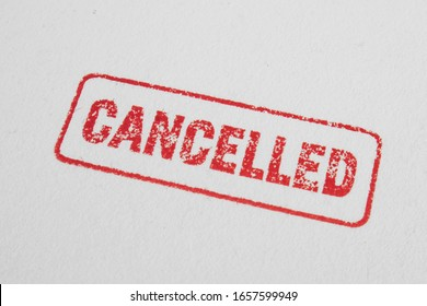 Cancelled stamp close up and isolated on white background. Cancelation message in red ink with border. Textured lettering on craft paper.