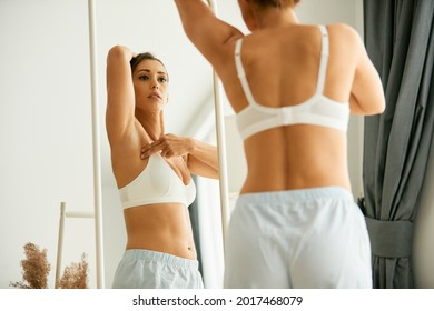Cancer aware young woman looking herself in a mirror while doing breast self-examination at home.  - Shutterstock ID 2017468079