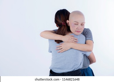 Cancer woman with no hair hug her friends or family to receive warm, love, care and will to fgiht with her severe diesease on white backgroun with copy space/ medial and care concept