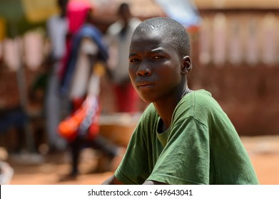 CANCHUNGO, GUINEA BISSAU - MAY 3, 2017: Unidentified local boy in green shirt frowns in the centre of Canchungo, one of the major cities of the country