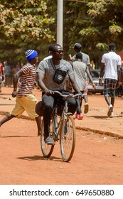 CANCHUNGO, GUINEA BISSAU - MAY 3, 2017: Unidentified local man rides a bicycle in the centre of Canchungo, one of the major cities of the country