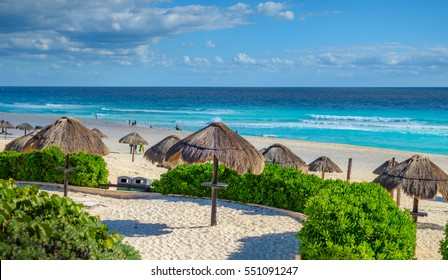 Cancun beach in mexico with umbrellas in the sand, beautiful blue water with dramatic clouds