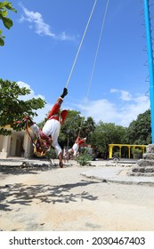 Cancun, Mexica 2014, a ritual dance-game among the Indians of Mesoamerica: five participants-voladores (Spanish volador — flyer), in costumes imitating bird plumage, are on a round rotating platform i