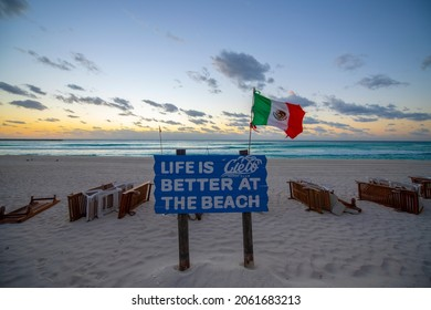 CANCUN, MEXICO - JAN. 20, 2020: Cielo Beach Club sign with Mexican National Flag waving on Chacmool Beach at sunrise, Cancun, Quintana Roo QR, Mexico.