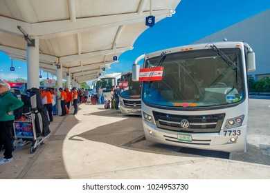 CANCUN, MEXICO - JANUARY 10, 2018: Unidentified people walking in the airport and some touristict busses parked at at the enter of Cancun International Airport, Mexico