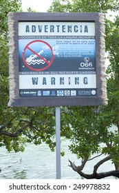 CANCUN, MEXICO - JANUARY 22, 2015: A sign is posted on the shore of the Nichupte Lagoon in Cancun warning of the presence of dangerous crocodiles throughout the lagoon