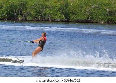 CANCUN, MEXICO - JULY 11TH, 2016: Athlete water skiing behind a boat. Man wakeboarding on a lake. Cancun Waterski Wakeboard School