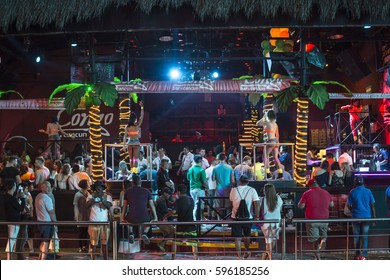CANCUN, MEXICO - MARCH 1, 2017: Spring breakers celebrate in a popular Cancun nightclub with a tropical interior and go-go dancers while spectators observe from outside.