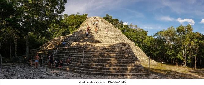Cancun / Mexico - November 2014: Tourists climbing the empty ancient Coba Maya Ruin in the thick jungle near Cancun, Yucatan, Mexico.
