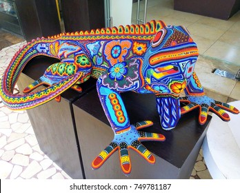 CANCUN, MEXICO - NOVEMBER 2017: Close-up of beautiful decorated colorful iguana made from beads – example of traditional huicholes art typical for Huichol People, native Mexican Indians