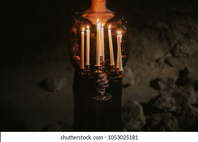 Candelabra in a cave with gothic chic woman
