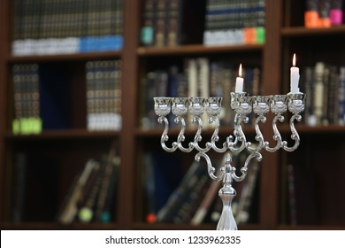 """The candelabrum known as a """"menorah"""" on the first night of candle lighting on the Jewish holiday of Chanukah, with a blur background"""
