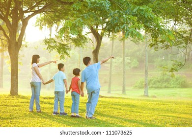 Candid Asian family pointing at outdoor park