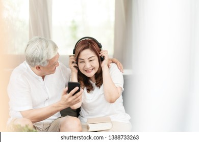 Candid of attractive older couple asian sitting relax together on couch at home in lifestyle of retirement people concept. Asian old man and senior woman listen to music on podcast from mobile phone.