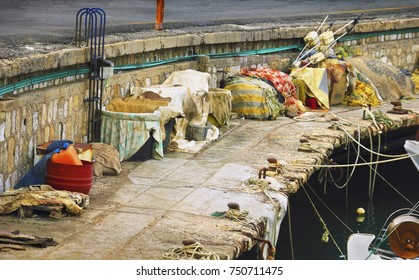 Candid cityscape - Fishing takle and nets rest on the background of the old city pier, Heraclion, island of Crete, Greece, Southern Europe