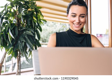 Candid closeup image of a happy business woman smiling and working with laptop in a cafe. Portrait of succesful young female manager working on laptop computer in resturant sending emails for clients.