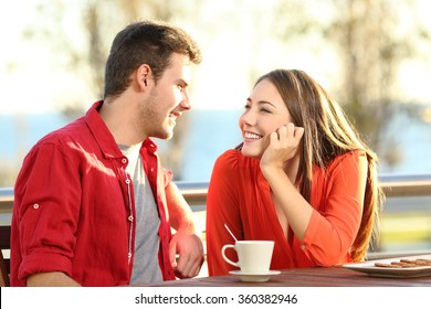 Candid couple date falling in love flirting in a terrace looking each other with tenderness thinking to kiss