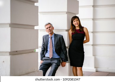 Candid, funny and light-hearted business portrait of an Asian Chinese woman and a mature Caucasian man leaning against a pillar of a legal-looking building.