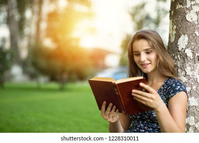 Candid happy woman sitting outside near a tree reading a book smile on face outdoors sunset and sunflare on green lawn headphones on head. Multicultural model mixed race asian russian girl. Copy space