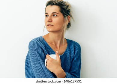 Candid image of attractive woman dressed in cozy knitted blue sweater with a mug of cappuccino. Beautiful young woman drinking hot beverage at home. Charming blonde female holding a coffee cup.