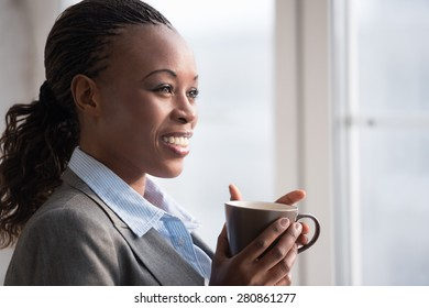 Candid image of a businesswoman drinking coffee while working at office. Selective focus.