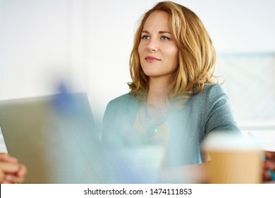 Candid image of succesful business woman caught in an animated brainstorming meeting