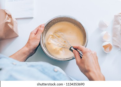 Candid image woman mixing batter, first person view. Female's hands holding bowl whisking milk, flour and eggs on white table.