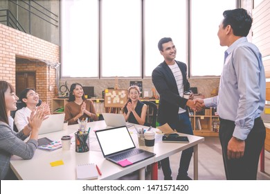 Candid of Indian creative design man smiling and shaking hands with coworker man or colleague and other clapping hand at office workplace. Introduction to team or marketing group concept soft tone.