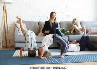 Candid indoor shot of frustrated young nanny babysitting four wild noisy naughty children who playing and fooling around, absolutely ignoring her. Female babysitter can't handle mischievous kids