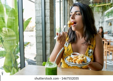 Candid lifestyle portrait of fashionable healthy ethnic businesswoman eating an organic vegetarian cauliflower dish for vegans and drinking green smoothie