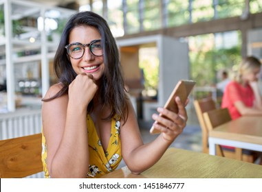 Candid lifestyle portrait of laughing hispanic millennial student typing on cellphone in modern trendy and bright cafe with plants