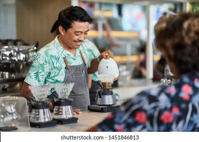 Candid lifestyle shot of smiling ethnic indonesian barista and small business owner preparing organic fair-trade coffee in bright trendy coffee shop wearing apron