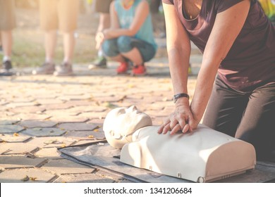 Candid of mature asian female or older runner woman training on CPR demonstrating class in outdoor park and put hands over CPR doll on chest. First aid training for heart attack people or lifesaver.