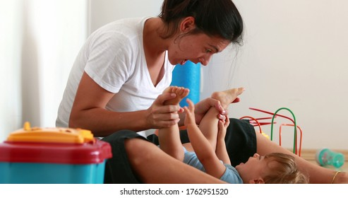 Candid mother playing peekaboo with infant child baby legs. Toddler and parent bonding