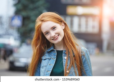 candid outdoor portrait of pretty smiling young girl with long red hair, morning sunrise light
