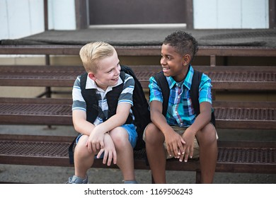 Candid photo of two students talking together at school. Smiling boys having fun together sitting on the stairs enjoying their friendship