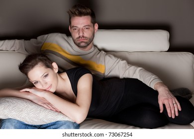 A candid photo of a young couple watching TV - no cheesy un-natural smiles