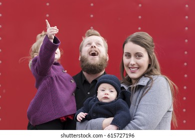 Candid photograph of young family isolated on red background.
