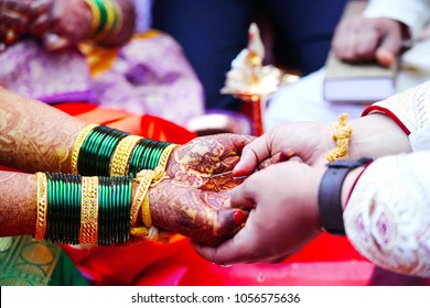candid photography image . they are playing rituals of wedding ceremony .focus on hands of groom & bride .