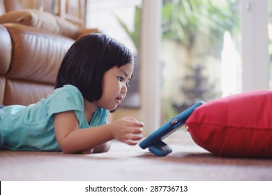 Candid picture of baby girl watching video on tablet