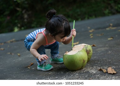 Candid picture of a little cute girl trying to insert straw on a coconut. Outdoor summer shot.