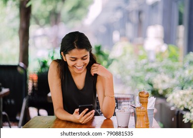 Candid portrait of an attractive, young Indian woman sitting in a cafe or coworking space on a sunny day. There are lush, green plants in the background. She's smiling and looking at her smartphone.