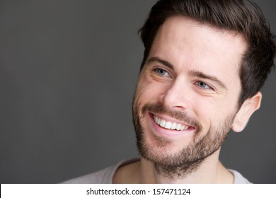 Candid portrait of an attractive young man smiling on gray background