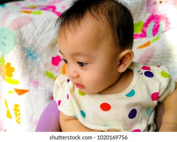 Candid portrait of a cute and expressive 7 month asian baby girl. Lifestyle and childhood concept.