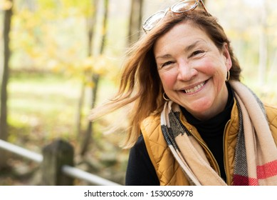 candid portrait of happy middle age woman hiking outdoors in autumn
